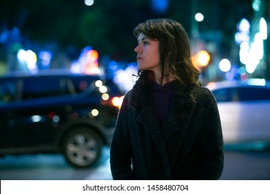 Caucasian pedestrian woman walking the street at night in the city with moving cars in the background.  She looks nervous or unsure like a lost tourist or afraid of commuting alone.