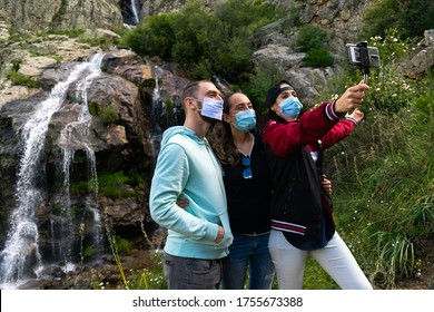 Caucasian people taking a selfie wearing mask in a waterfall in the nature. Group of people travelling around Europe during the coronavirus (covid 19) health crisis wearing sanitary mask. Eco turism