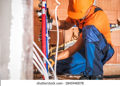 Caucasian Plumber Wearing Orange Hard Hat Installing Bathroom Water Supply Inside Newly Developed Concrete Blocks Building. Construction Site Theme.