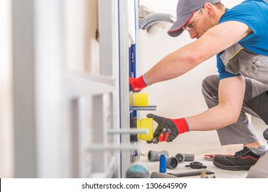 Caucasian Plumbing Worker Installing Toilet Bowl and Sanitary System Inside the House.