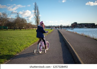 caucasian pre school age girl on the pushbike newxt to a path by the river bank, looking back over her shoulder