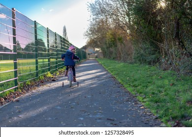 caucasian pre school age girl on the pushbike newxt to a path next to a fenced playground and row of trees