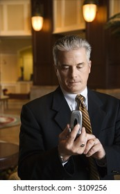 Caucasian prime adult male businessman dialing cellphone in hotel lobby.