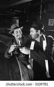 Caucasian prime adult retro males sitting at bar drinking.