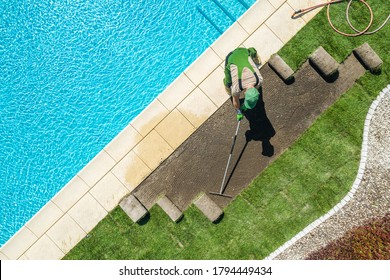 Caucasian Professional Landscaper Installing Brand New Grass Turfs Around Residential Swimming Pool. Raking Soil Before Installation. Gardening and Landscaping Industry Theme.
