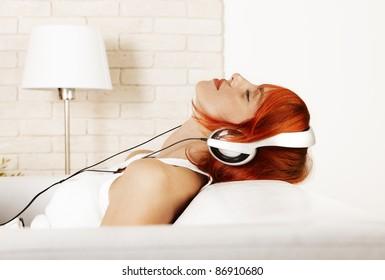 Caucasian redhead woman wearing headphones and listening music