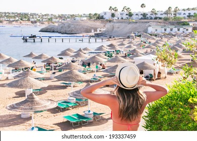 Caucasian resting girl is standing and enjoying view  of ocean and beach with parasoles. Happy relaxing female model in red bikini and white hat. Summer vacation concept (Sharm El Sheikh, Egypt).