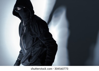 Caucasian Robber in Black Mask and Black Gloves Preparing for Robbery.