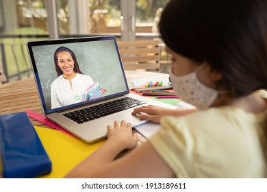 Caucasian schoolgirl wearing face mask and using laptop on video call with female teacher. Online education staying at home in self isolation during quarantine lockdown.