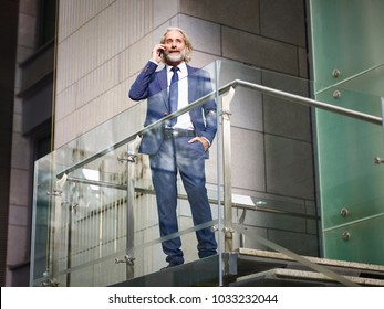 caucasian senior corporate executive standing on top of stairs making a call using mobile phone in modern office building, low angle view.