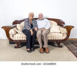 caucasian senior  couple in love sitting on a sofa