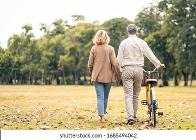 Caucasian senior elder couple love to hold hand and carry bicycle walk in park. Mature are happy and enjoy with slow life. Two people delight activity together. Retirement family lifestyle concept.