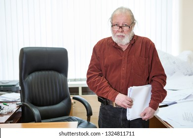 Caucasian senior man dressed in brown shirt standing near leather chair with blueprints in hands