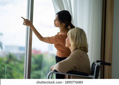 Caucasian senior patient woman on wheelchair with mixed race daughter in bedroom