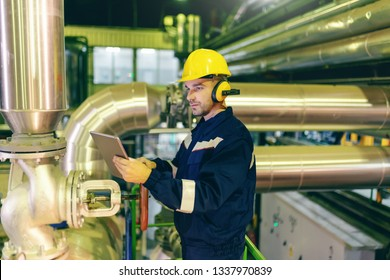 Caucasian serious hardworking worker in protective suit and helmet on head using tablet while standing in heavy industry plant.