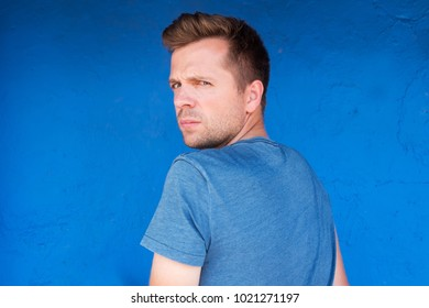 Caucasian serious man in blue t-shirt turning back. He is sad and offended. Concept of being alone without friends