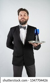 caucasian servant with a beard in a formal business suit stands with a steel tray in his hand and a glass of wine on a white solid background in the Studio