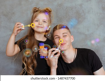 caucasian siblings - teenager boy brother and little girl sister with bubbles in modern loft interior on gray cement background