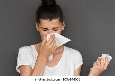 Caucasian sick woman wearing white Tshirt, caught cold and sneezing into tissue. Pretty female have headache, virus against gray background. Healthy, medicine concept. Copy space for text, advertising