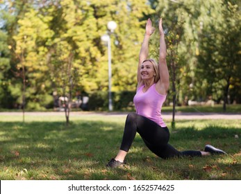 Caucasian smiling happy woman doing yoga on the grass outdoor in urban park, selective focus. Fitness, stretching, aging, healthy lifestyle, sport, antistress and activity concept