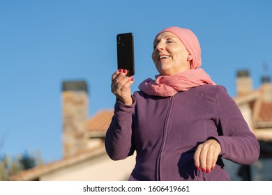 caucasian smiling senior woman with a pink head scarf talking with the phone