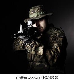 caucasian soldier with rifle dark background
