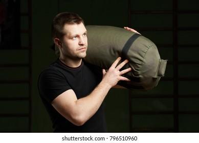 Caucasian sport man portrait. Man carrying sand bag on shoulder