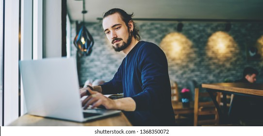 Caucasian student watching webinar on laptop computer improving skills on programming, serious professional web designer working on freelance sitting in cafeteria and using good wifi connection