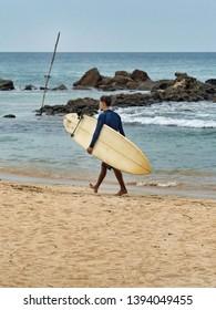 Caucasian surfer walking on the beach in Mirissa . Sri Lanka, March 17, 2019.
