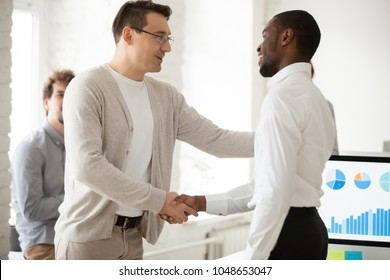Caucasian team leader or company boss promoting successful african manager handshaking expressing gratitude, executive shaking hand of black employee appreciating for good work results or rewarding