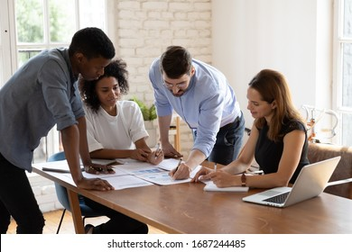 Caucasian team leader share project idea to multi-ethnic workmates, workgroup brainstorming discussing planning corporate strategy, doing paperwork, reviewing financial data at office meeting concept