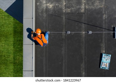 Caucasian Technician Wearing Orange Uniform and Hard Hat Installing Lightning Protection System Rod on Top of Commercial Building. Protect Structure From Elements.