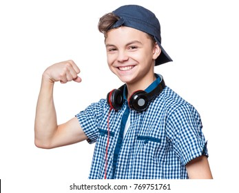 Caucasian teen boy showing off his biceps. Happy teenager with cap and headphones showing his hand biceps muscles strength, isolated on white background.