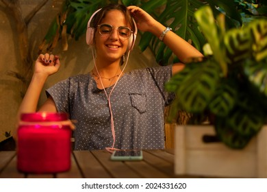 Caucasian teen girl smiling and dancing while listening to music on her smartphone. Front view. Horizontal. With copy-space.