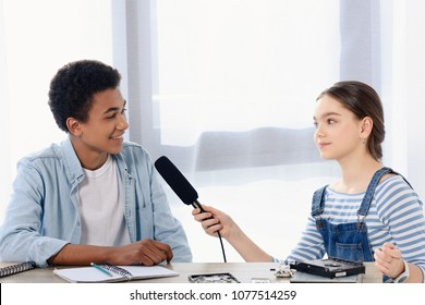 caucasian teen kid conducting interview with african american friend for vlog at home