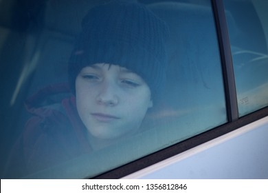 Caucasian teenage boy in back seat of a car looking through the window