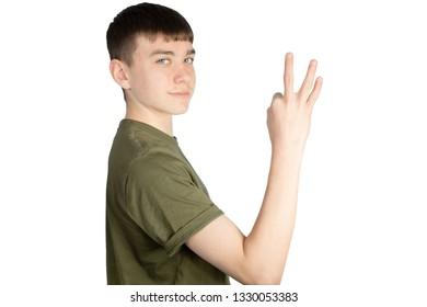 Caucasian teenage boy doing British Sign Language showing the symbol for 3