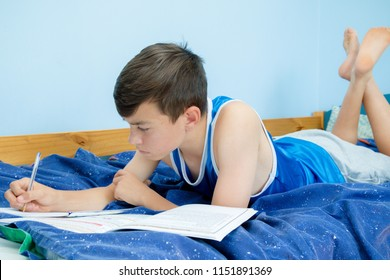 Caucasian teenage boy laying on his bed doing homework