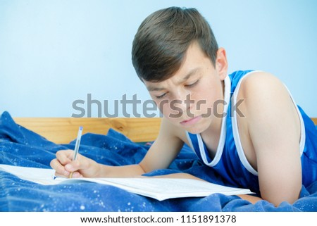 Caucasian teenage boy laying on his bed reading a textbook