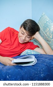 Caucasian teenage boy reading a book laying on a bed supporting his head