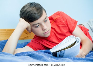 Caucasian teenage boy reading a book laying on a bed