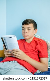 Caucasian teenage boy reading a book sitting up in bed