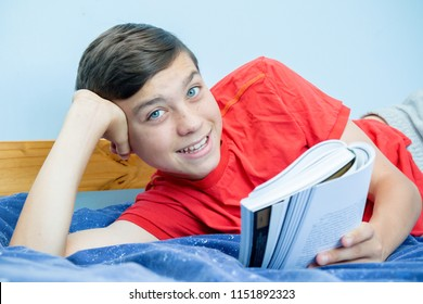Caucasian teenage boy reading a book laying on a bed laughing