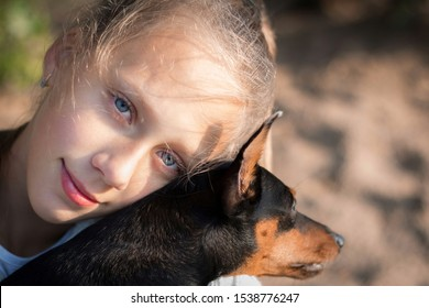 Caucasian teenage girl with big blue eyes hugs mini pinscher puppy against sand background in sunny summer day