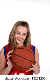 Caucasian teenage girl in a red jersey, holding a basketball against a high key background.