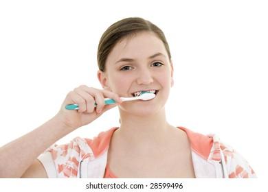 Caucasian teenager brushing her teeth on white background