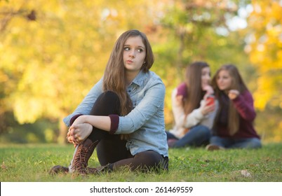 Caucasian teenager wondering about girls talking behind her