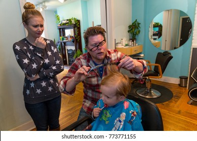 Caucasian Toddler Boy Has His Hair Cut By A Barber As His Mom Watches