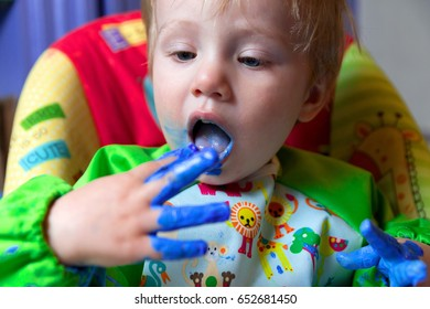 Caucasian Toddler Boy Wearing a Smock Mixes, Plays with and Finger-paint's on White Paper