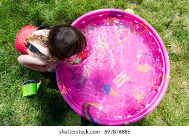 Caucasian Toddler Brown Haired Girl Plays In A Pink Backyard Kiddie Pool During  A Hot Summer Day